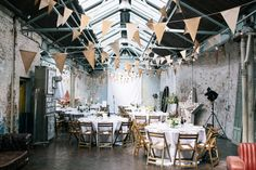 Exposed brick industrial reception room with urban decor - Image by Lee Robbins Photographic - David Fielden Wedding Dress & Jimmy Choo Shoes for an urban, industrial wedding at MC Motors London City with pastel bridesmaid gowns & Groom in a Vivienne Westwood Suit.