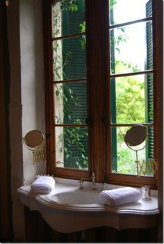 marble sink with just under beautiful paned windows, nickel hardware, mounted expanding mirrors, hand towels folded, wonderful idea to put on makeup in natural light if mirrors were mounted just a little higher
