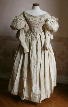 The website says 1834, but the top of the sleeves and the pointed bodice lead me to place it later.  Follow the link for more images.