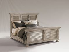 Decorative louvered panels in the headboard and footboard with transitional corbel supports and cornice cap rails. Side rails feature raised panel molding, with decorative molding around the entire perimeter of the base. Select hardwoods and veneers with a weathered textured surface. Finish: Driftwood
