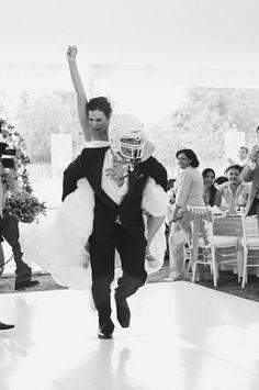 novio usando un casco de futbol americano mientras carga su una novia en la espalda
