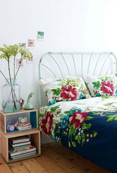that big bold floral print takes center stage and holds it own.  I do also love the chippy aqua metal bedframe and other pale seafoam in the accessories.