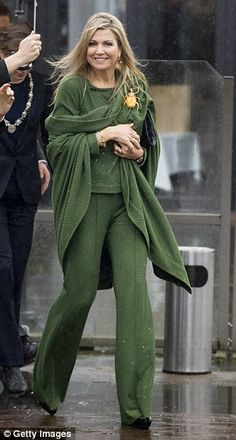 With such an outlandish accessory the Queen kept the rest of her ensemble relatively simpl...