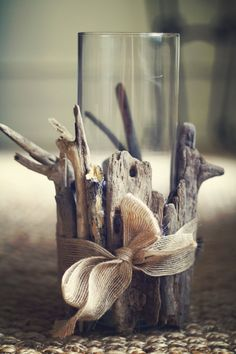 Collect some beautiful driftwood, some fabric/yarn and tie it up.  Add a pillar candle for craft perfection!