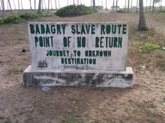 """Badah - """"To create""""; Garah - """"Misery, strife, trouble""""; Gari (Gary) - """"My misery""""; Loosely translated the Hebrew word Badagry means """"the beginning of my trouble"""". Amen. Notice a tombstone marks the spot where many of our ancestors were either forced or tricked onto slave ships bound for places unknown to serve out a life of misery and sorrow enriching others."""