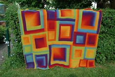 Oh my goodness. Multi-sized mitred squares knitted in Kauni rainbow yarn, and then made into a blanket. I want!