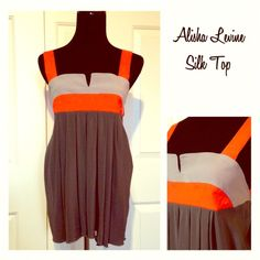 ✨Gorgeous Alisha Levine Color-Block 100% Silk Top✨ 100% silk. Great shades of grey and orange make for a unique fun color combo anytime of year! Tank sleeves meet w/ a cool strap across back w/ 2 snap closure. Back is open at top, elastic around mid back gives stretch & is slightly rounded then flows nicely to hem. Back slightly longer than front. EUC. 2 SMALL issues as shown in photo 4, name brand tag is loose on one side, & slight pull or loosening of elastic at mid-back hem where meets…