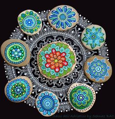 Yesterday i painted this mandala flower on the center  Love the picture also how it came out beautiful with my other #paintedstone flowers on my black&white ink #mandala on black paper