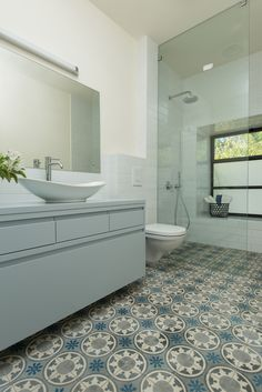 A modern styled bathroom with a teal color scheme. By Liat Hadas, Architecture & Design.