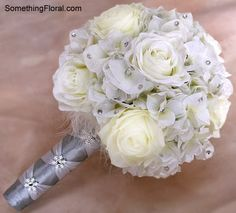 Winter Wedding Bridesmaid Bouquet. Ultra realistic, artificial white and cream roses and white, crystal-encrusted hydrangea with a hint of glitter spray for a freshly fallen snow sparkle. The base of the bouquets were finished with fluffy white maribou feathers and light and medium silver satin French braid style stem wraps accented with white and crystal snowflake accents. Designed by Something Spectacular/Something Floral, Warren, MI