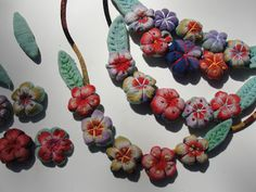 Art Spirit: Busy stitching.... Necklace made from flowers cut from a Japanese scarf, made into yo yos, stuffed, sewn and then embroidered. Ingenious.