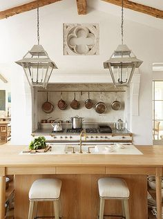 Above the Lacanche range, copper and stainless-steel cookware is within easy reach. The stone quatrefoil is from Belgium, and limestone was used for the range's backsplash.