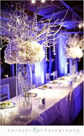 Winter tall centerpiece with dangle's of crystal' s and mums made with branch's giving that winter wonderland feel.