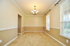 two tone dining room with chair rail light color above dark color
