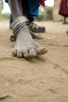 an older woman's feet -- she belongs to a traditional Maasai tribe {Tanzania, Africa}