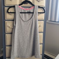 New Balance light gray workout tank New balance size medium loose fitting light gray workout tank. Has hot pink detailing inside. 95% polyester 5% spandex. In really good shape, as I didn't wear it much. New Balance Tops Tank Tops