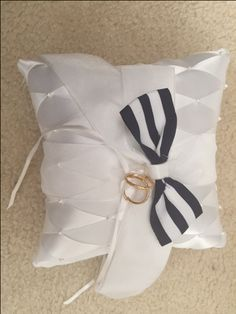 """White Ring Bearer Pillow with a bow of your color (as per picture). This can be taken out without harming the entire look.   Put silver or gold """"fake"""" rings."""