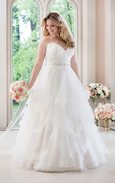 """This A-line wedding dress from Stella York features Royal organza and a fitted, Diamante-encrusted lace bodice with a sweetheart neckline. The 1/2"""" grosgrain ribbon waist belt slims, while the mid-cut back zips up with ease under sparkling Stella crystal buttons. The skirt adds ethereal appeal with its flowing layers of tulle."""