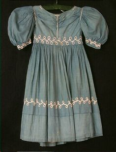 """Dress, boy's, blue cotton chambray,  1829-1830, Light blue cotton chambray; empire waist with inset 2"""" waistband; cartridge pleated skirt; elbow-length cartridge pleated sleeves with 1"""" cuffs; wide scoop neck; bodice gathered horizontally from shoulders to center of bodice under chin; 1.5"""" growth tuck taken in on skirt 6"""" up from bottom; scrolled white soutache around waistband, cuffs, and above tuck,  bodice portion lined in white cotton; closes with brass hooks and eyes up center back."""