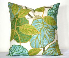 These pillow covers display large lime green, turquoise and green leaves on a white background. The designer textile by Robert Allen has the look of