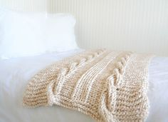Knit this EASY cabled throw with new Lion Brand Color Clouds! Big stitches make this a great project for first-time cable knitters - get the free pattern from Mama in a Stitch!