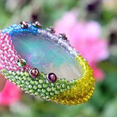 Barbara+Barvami+jen+září+tento+náhrdelník,+který+vznikl+obšitím+skleněného+kabošonu,+rovněž+plného+barev.+Na+obšití+jsem+použila+kvalitní+japonský+TOHO+rokail+v+barvách+sytě+růžová,modrá,+jemně+fialová,+žlutá+a+zelená,+a+duhově+se+lesknoucích+koleček.+Přívěšek+je+zavěšen+na+hedvábné,+ručně+barvené+šňůrce+Pongé,+zelené+barvy+a+je+podšitý+velmi...