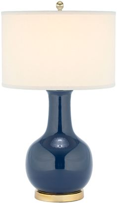 This lamp is sure to illuminate any room with elegance and style. Its classic gourd body of navy blue glazed ceramic is accented with gold-finished metal neck and base, and topped with a hard white dr