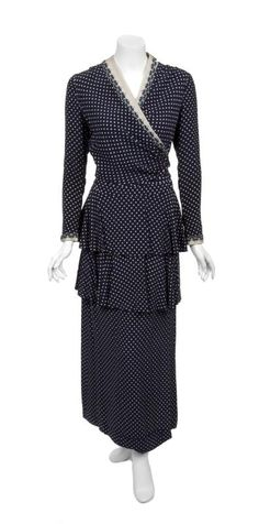 A full-length, long sleeve, silk navy and ivory polka dat dress worn by Bette Davis in The Corn is Green (1945). The dress has a wrap-style bodice with linen trim on the cuffs and collar line and two tiers of silk over a straight skirt