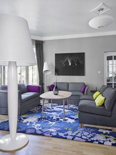 Dis. interiørarkitekter have designed the Norwegian Official Residence in Tallinn, Estonia.  Beautiful rug in organic pattern of blue, white, green, lavender.  Gray sofa couches with accent pillows in purple and lime green.