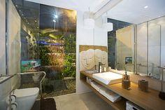 Vista do banheiro com jardim vertical ao fundo. Casa Container Vitória.
