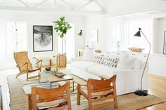 Neutral living space with a white sofa, leather chairs, a large woven rug, and exposed wooden beams