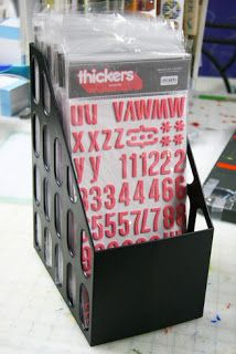"Use an extra wide magazine upright holder. The Thickers packaging is about 6 1/2"" wide or 16 cm, so when looking for the holder just measure the inside to be at least that wide."