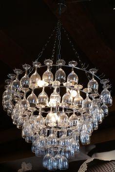 Hanglamp gemaakt van een groot frame van een lampenkap en veel wijnglazen. De dragers waar de glazen aan hangen moet je wel goed kunnen buigen