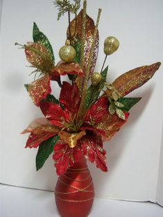 "Red and Gold Glittered Glory Holiday Christmas Floral Arrangement. $25.00, via Etsy. This arrangement is approximately 18"" high and is in a weighted glass vase in a matte red color with raised gold glittered bands encircling it. The lucious designer poinsettias are multi-layered with organza overlays and lots of gold trim."
