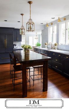 Beautiful kitchen features dark gray cabinets painted Benjamin Moore Raccoon Fur adorned with gold pulls paired with Super White Quartzite countertops and a full height carrera marble tiled backsplash.