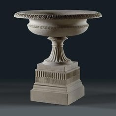 stone Blashfield Urn on a raised and fluted pedestal is a reproduction based on an urn from the 1850s by J.M. Blashfield