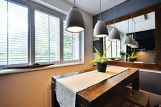Combined living, dining and kitchen space in a modern black & grey kitchen in a small London apartment. High gloss black, Franke sink, reflective surfaces, rustic concrete bench. Concrete lights, dining, shutters, stripes.