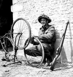 A Canadian soldier fixing up his bike; Normandy, France - 20 June 1944