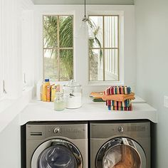 low, front load washer and dryer with counter on top and mirrored window panes above.