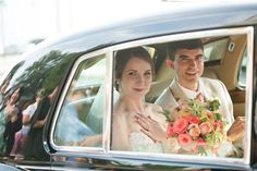 A happy bride and groom head to their reception. Bouquet by Regalo Design. Pink and coral bride's bouquet.