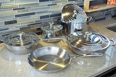 A light beige kitchen countertop with blue and beige tile backsplash, with a variety of stainless steel cookware on the countertop. Refinish Countertops, How To Install Countertops, Laminate Countertops, Concrete Countertops, Kitchen Countertop Materials, Kitchen Countertops, Stainless Steel Pot, Beige Kitchen, Pots And Pans Sets