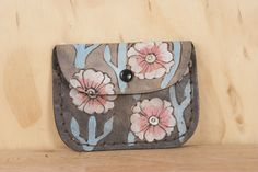 A tiny piece of functional art, the handmade leather Aurora Stitched Pouch has flowers and vines covering the entire thing in bright, bold colors, making it easy to find inside your purse. Perfect for keeping loose change, jewelry, or any small items you don't want floating at the bottom of your purse, or you can even use it as a small wallet on its own.