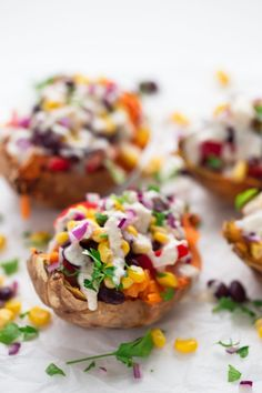 7-ingredient vegan stuffed sweet potatoes with black beans, corn, tomato, onion, parsley and a creamy tahini dressing. A hearty gluten-free dinner recipe.