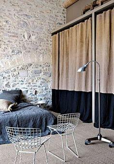Cloisonner la penderie avec de lourds et épais rideaux pour cacher les vêtements. Ces épais rideaux donnent un effet de hauteur et isolent du froid du mur en pierres apparentes