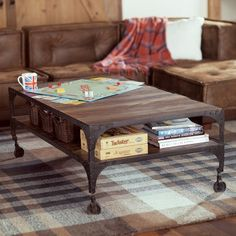 Railway Coffee Table  Crafted with distressed wood planks and iron legs and trim, it has the look of a well-worn, vintage piece