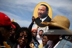 A marcher holds a picture of Dr. Martin Luther King Jr. before walking across the Edmund Pettus Bridge during the 50th anniversary commemoration of the Selma to Montgomery civil rights march on March 8, 2015 in Selma, Alabama. Tens of thousands of people gathered in Selma to commemorate the 50th anniversary of the famed civil rights march from Selma to Montgomery that resulted in a violent confrontation with Selma police and State Troopers on the Edmund Pettus Bridge on March 7, 1965.