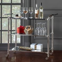 A 1930s industrial trolley lent its lines to our refined design in tempered glass and polished metal. Three roomy shelves offer ample space for a cocktail bar, a brunch buffet or afternoon tea service, and swiveling casters let you serve a movable feast. Leather-wrapped handles add an unexpected touch of texture