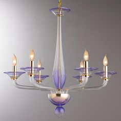 """Amethyst Glass Chandelier - Large A gorgeous combination of jeweled tone amethyst glass and modern gold accents create this posh chandelier. The mod shapes and bold curves add to the delicious pop of color and amazing glamorous style. This chandelier is true modern elegance at it's finest. 6x60 watt candle base lamps max. (28""""Hx30""""W)"""