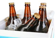 Traveling refrigerator with beer bottles and ice cubes isolated