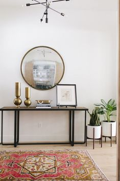 Love the modern pendant light, round mirror, modern console, midcentury plant stands and vintage tan and coral rug in this bright entryway.